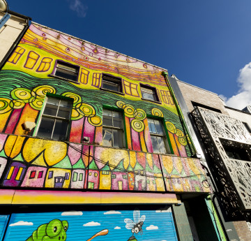 high street building covered in a bright painting in Swansea