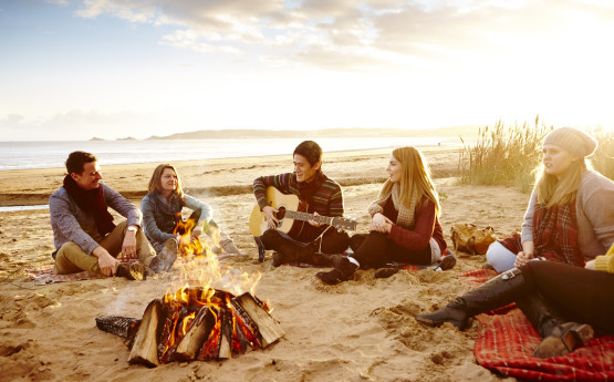 students relaxing on the beach around a campfire, one of them is playing a guitar