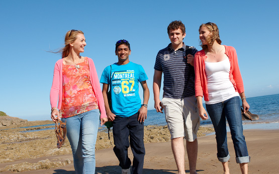 Students walking on the Swansea beach in the sun.