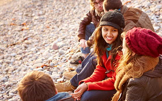 Students on a beach socialising.