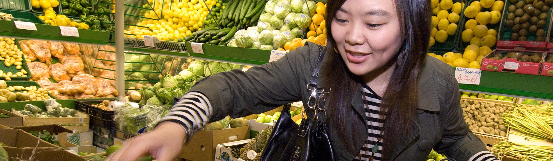 Student picking out vegetables in a supermarket.
