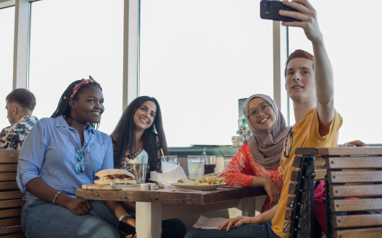 Students taking a selfie in a mumbles cafe