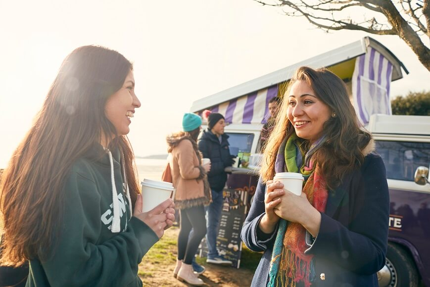 Students at the coffee campervan by the beach in winter