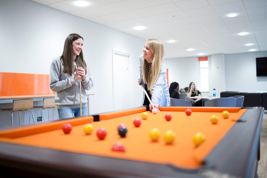 Students playing pool in accommodation common room