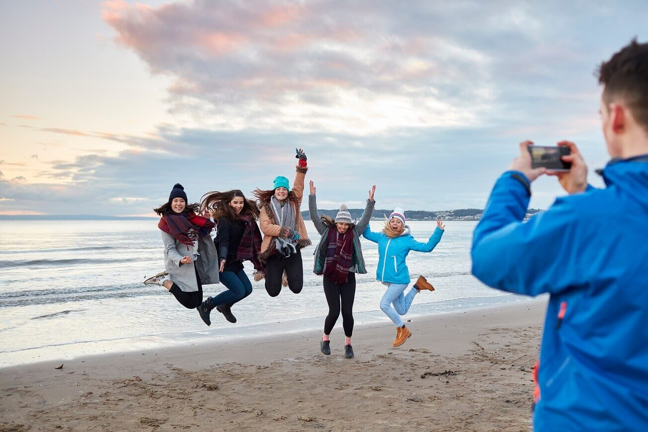 Students jumping for joy on the beach in winter