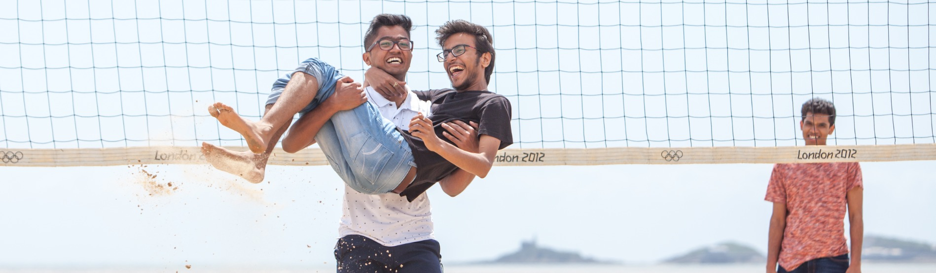 2 International students celebrating at a beach volleyball game in Swansea