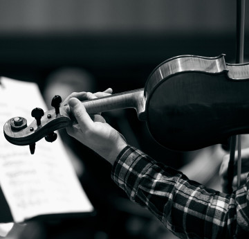 a black and white image of someone playing the violin